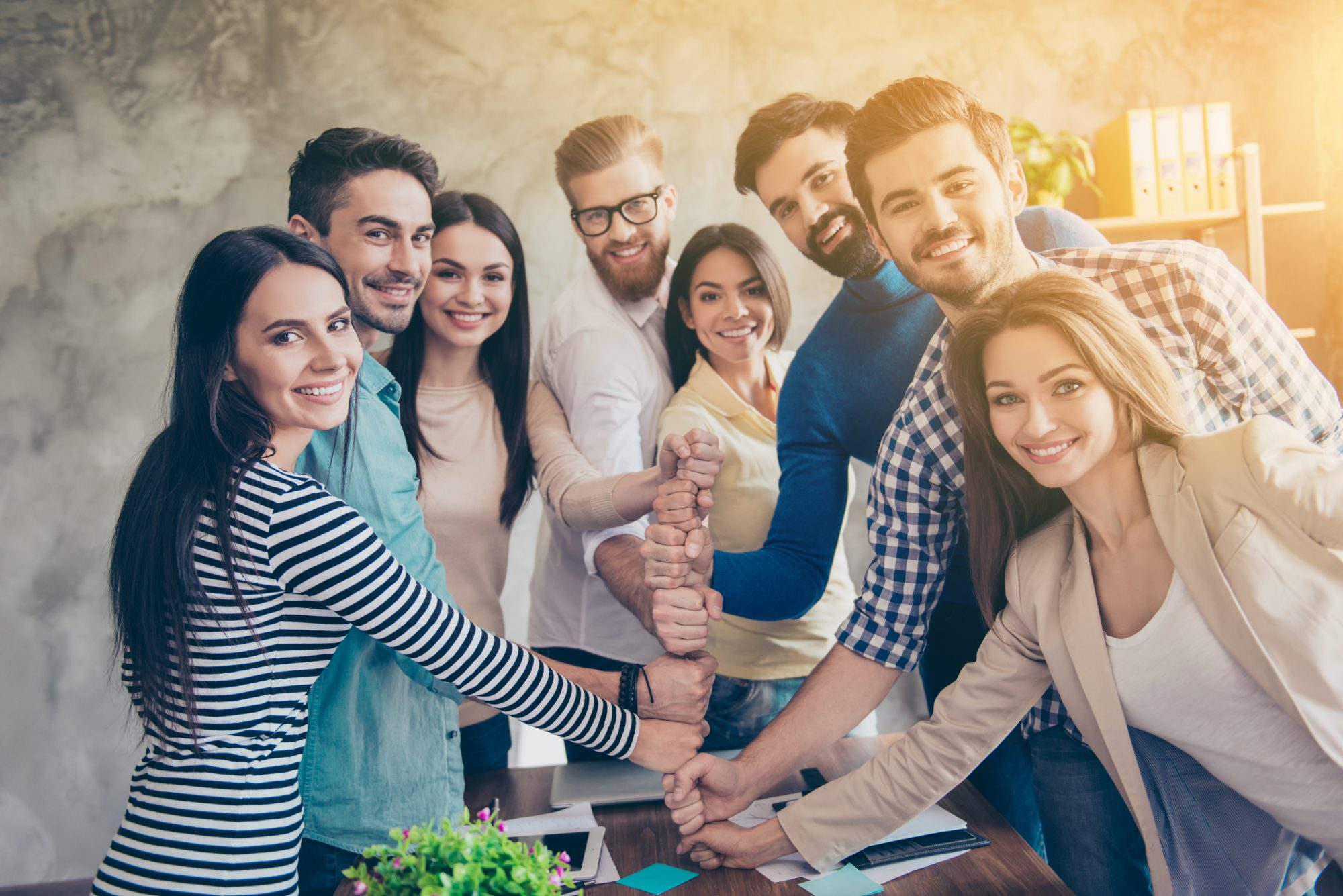 Conception of successful team-building. Close up of businesspeople putting their fists on top of each other on the desktop in nice light workstation, wearing casual clothes