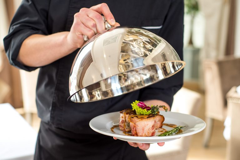 A chef or vaiter holding and shows a dish